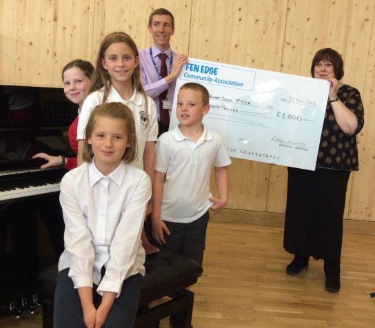 Fen Edge Community Association present a cheque to Cottenham Primary School towards a new piano